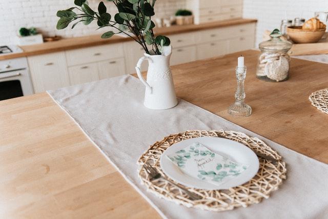 bílá kuchyňská linka s rustikálními úchytkami a kovový džbán
